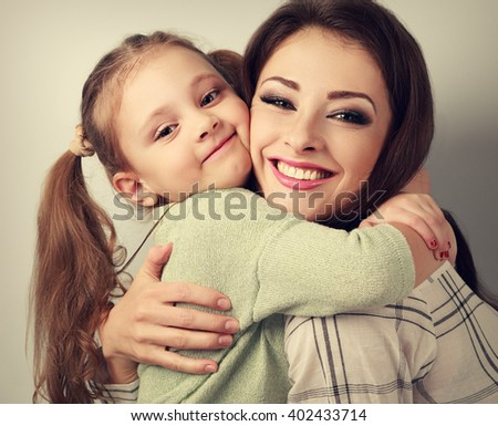 Happy smiling mother cuddling playful emotional kid girl in studio. Toned closeup portrait - stock photo