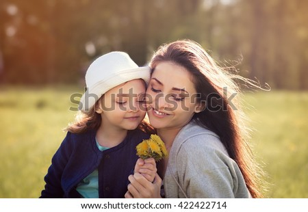 Happy smiling mother embracing her daughter and looking on yellow bright flowers on summer nature background - stock photo