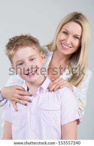 Happy smiling mother hugging young son with disheveled hair in the studio - stock photo