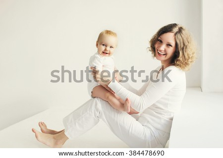 Happy smiling mother playing with baby at home in white room - stock photo
