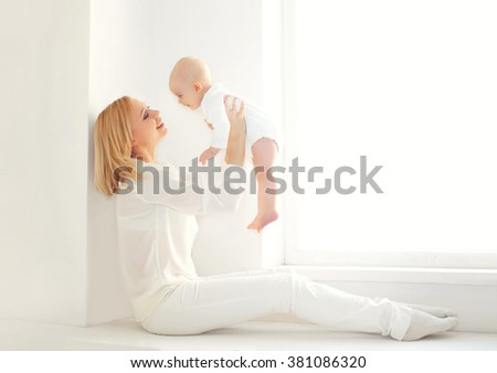 Happy smiling mother playing with baby at home in white room near window - stock photo