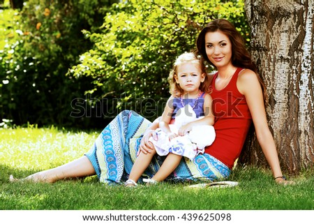 Happy smiling mother sitting with her sweet little daughter on a lawn. Outdoors.