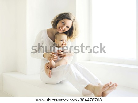 Happy smiling mother with baby at home in white room near window - stock photo