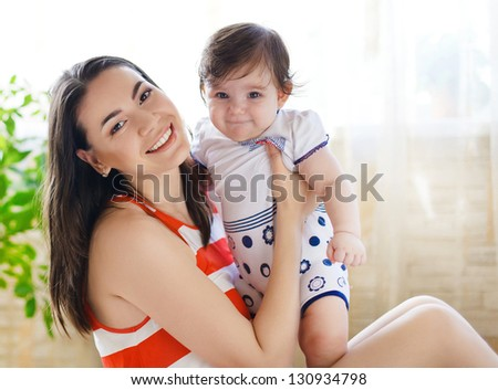 Happy smiling mother with eight month old baby girl indoor - stock photo