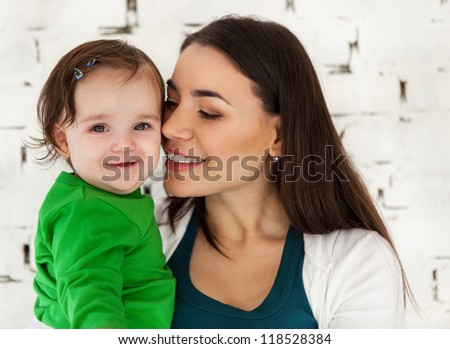 Happy smiling mother with eight months old baby near white brick wall - stock photo