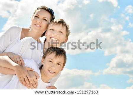 Happy smiling mother with her sons on sky background