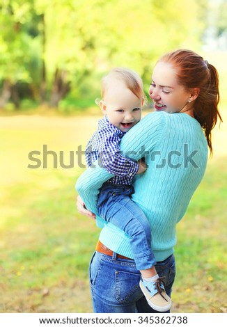 Happy smiling mother with son child together outdoors in park