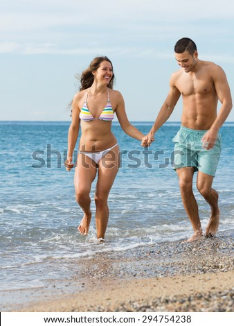 Happy smiling newly married couple having fun at the beach in honeymoon