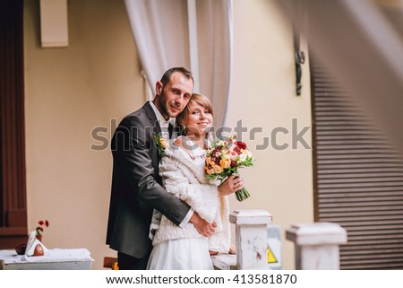Happy smiling newlywed couple sitting and kissing on terrace with bouquet