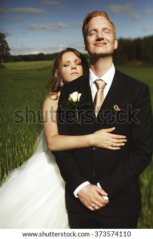 Happy smiling newlyweds walking on the meadow, wedding day