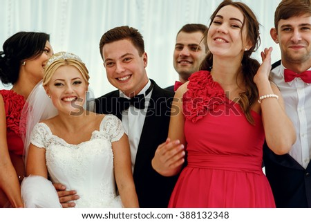 Happy smiling newlyweds with their friends on the wedding ceremony
