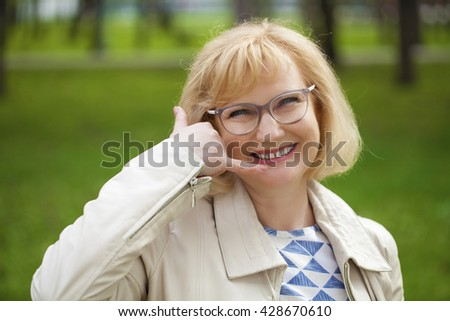 Happy smiling old blonde woman with call me gesture, against green summer park - stock photo
