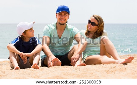Happy smiling parents and son sitting at sandy beach in summer day  - stock photo