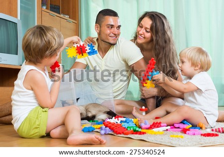 Happy smiling parents and two daughters plays with meccano set in home  - stock photo