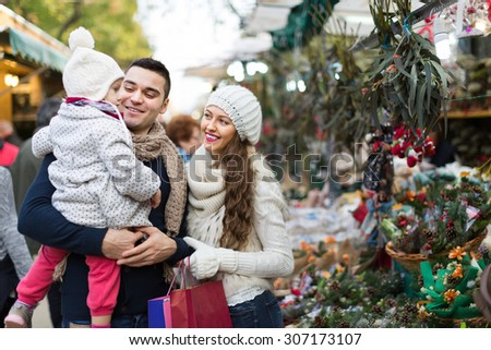 Happy smiling parents with little daughter at counter with Poinsettia. Shallow focus