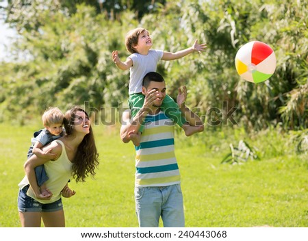 Happy smiling parents with little daughters playing together outdoor - stock photo