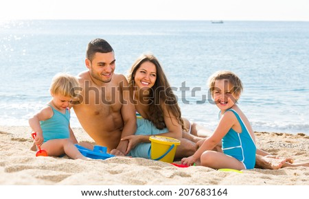 Happy smiling parents with two kids resting at beach in sunny day - stock photo