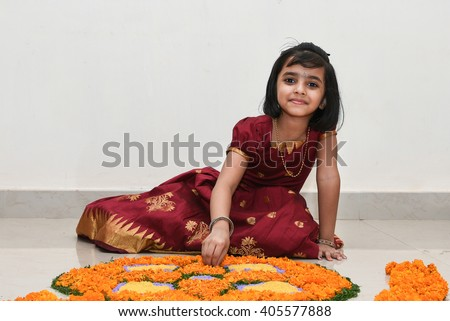 Happy smiling playful young Indian / South Indian girl wearing traditional dress holding / making  flower design/ bed  for Onam, Vishu Kerala India. Beautiful daughter/ kid in Indian sari. Asian child - stock photo