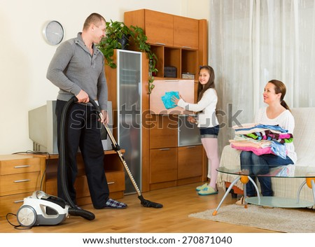 Happy smiling preschooler girl helping parents to clean at living room. Focus on man - stock photo