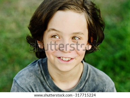 happy smiling preteen boy with long hair