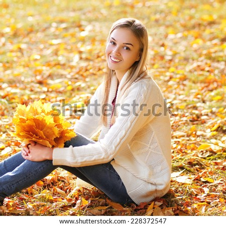 Happy smiling pretty girl having fun outdoors in autumn day