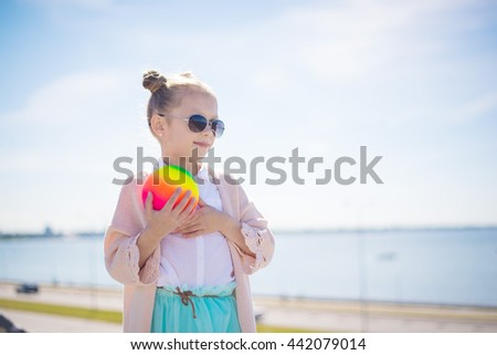 Happy smiling pretty girl portrait with ball in her hands with great beautiful sea landscape at summer sunny day - stock photo