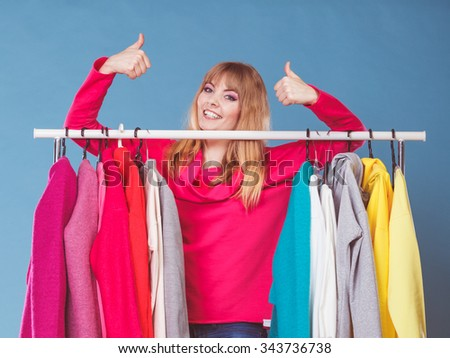 Happy smiling pretty woman choosing clothes to wear in wardrobe with thumb up gesture. Gorgeous young girl customer shopping in mall shop. Fashion clothing sale concept.