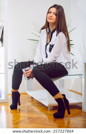 Happy smiling relaxing young woman on living room background.