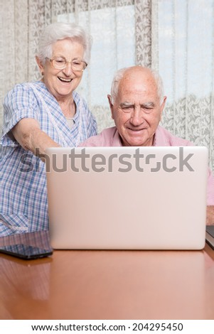 Happy smiling retired couple using computer laptop at home - stock photo