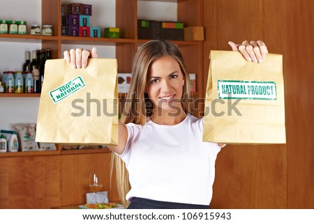 Happy smiling sales lady holding two paper bags in a store