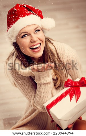 Happy smiling Santa girl with gift box enjoying falling snowflakes. Portrait of young pretty Caucasian woman celebrating Xmas and Happy New year at home.   - stock photo