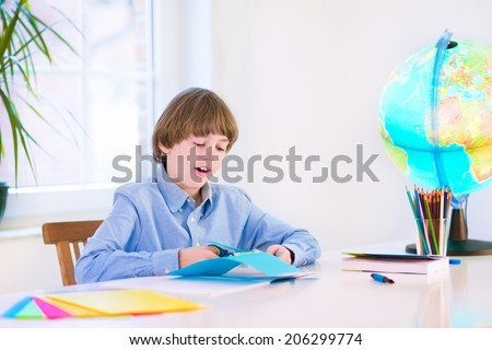 Happy smiling school boy, smart student, doing homework cutting paper, writing, drawing and reading a book at a white desk with a globe next to a window, back to school concept - stock photo