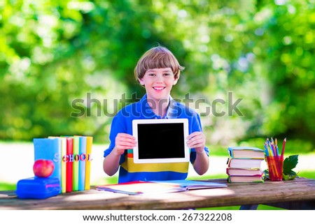 Happy smiling school boy, smart student, holding a white touch screen tablet computer relaxing on a school yard lawn reading books , playing games and having apple for lunch, copy space for your text - stock photo