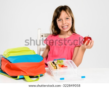 Happy smiling school girl holds red apple over her healthy lunchbox filled with fresh fruit and sandwich - stock photo