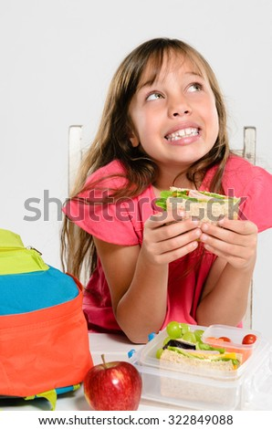 Happy smiling school girl looking up while holding healthy sandwich out of lunchbox filled with wholesome nutritious food - stock photo
