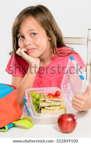 Happy smiling school girl opens her healthy lunchbox filled with fresh fruit and sandwich - stock photo