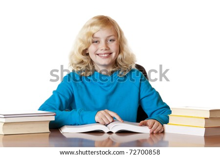 Happy smiling school girl sitting at desk reading books. Isolated on white background.