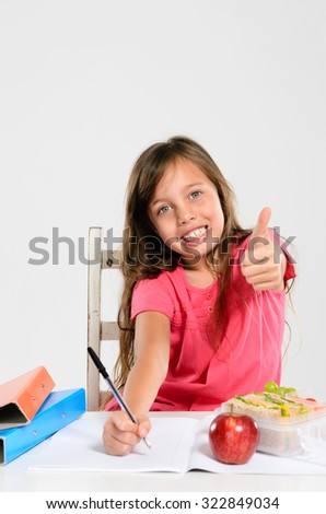 Happy smiling school girl studying, writing into her book and giving a thumbs up - stock photo