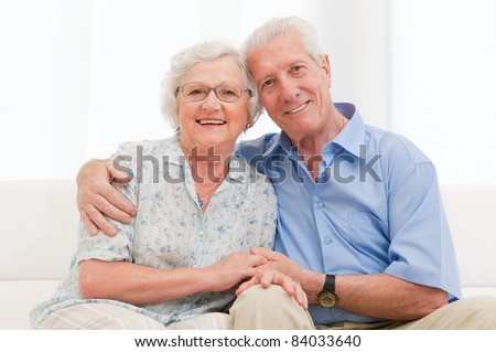 Happy smiling senior couple embracing together at home - stock photo
