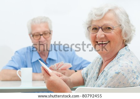 Happy smiling senior couple playing cards together at home - stock photo