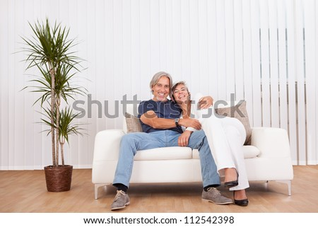 Happy smiling senior couple sitting in a close embrace beaming with vitality and enjoyment of their retirement
