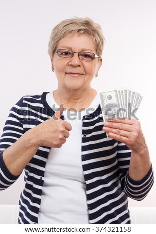 Happy smiling senior woman, an elderly pensioner holding currencies dollar and showing thumbs up, concept of financial security in old age