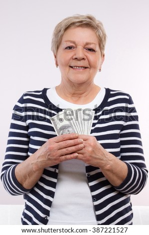 Happy smiling senior woman, an elderly pensioner holding currencies dollar, concept of financial security in old age
