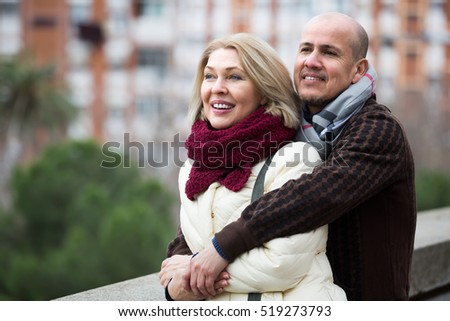 Happy smiling senior woman and elderly man posing together outdoors