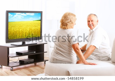 Happy smiling seniors couple watching TV at home - stock photo