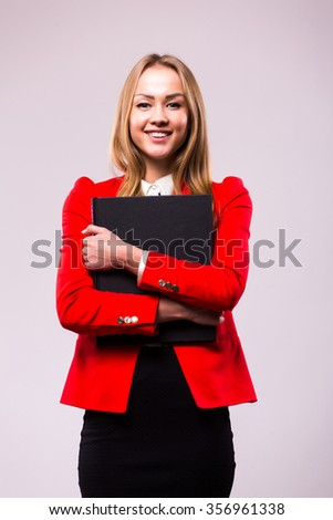 Happy smiling showing businesswoman with folder, against grey background. - stock photo