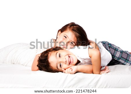Happy smiling siblings brother sister together laying. - stock photo
