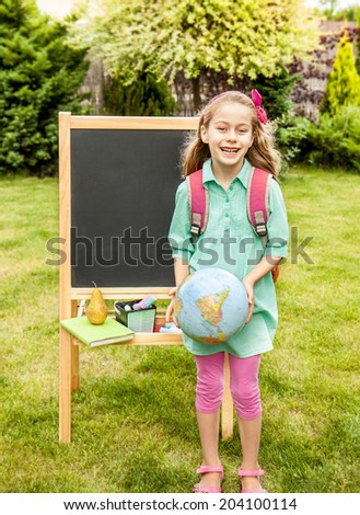 Happy smiling six years old blond caucasian child girl standing outdoor in front of the chalkboard - back to school, education concept. - stock photo