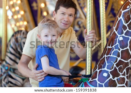 happy smiling son and his handsome father spending fun time together at amusement park riding merry-go-round - stock photo
