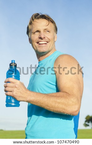 happy smiling sportsman holding a blue water bottle.